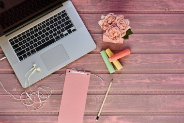 Women desktop with various objects. Laptop, cup of coffee, flower and blank paper lying on office desk. Workspace of creative person. Top view desk mock up with gadgets with copy space.