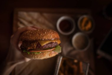 Tasty burger and french fries on wooden table. Burger cooked barbecue served on craft paper. American bbq food. Big hamburger with meat and vegetables. Unfocused at background. Street food, fast food.