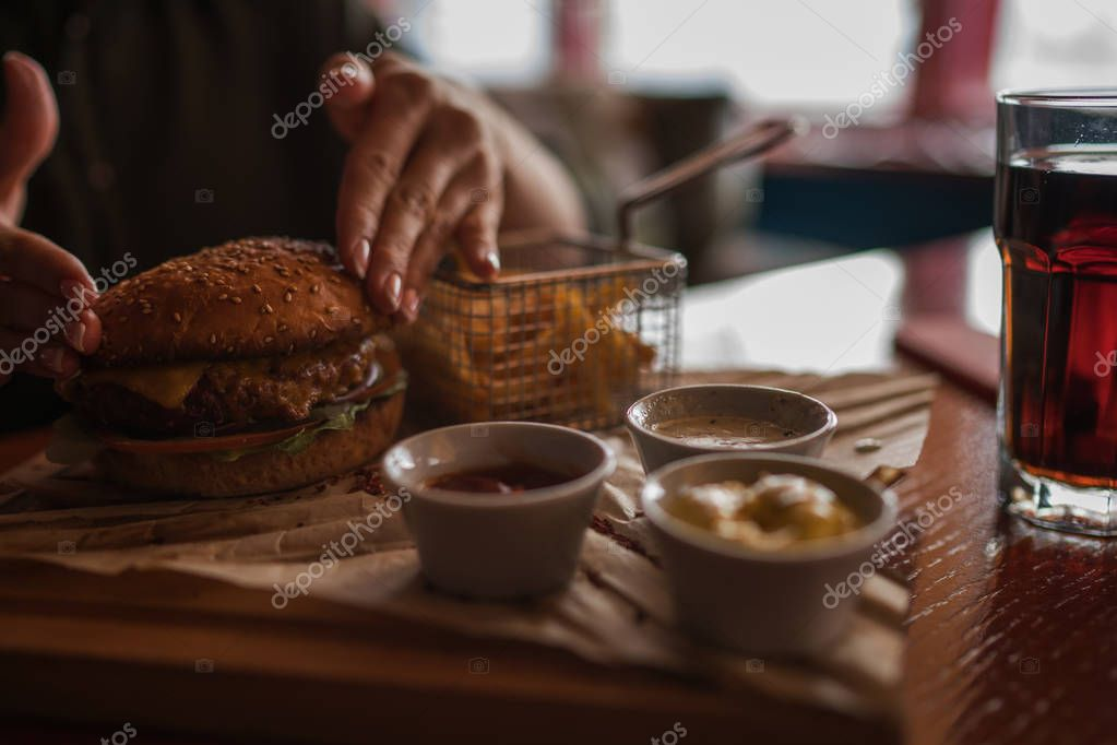 Woman holds burger with hands and fries on the background in cafe. Fresh burger cooked at barbecue in craft paper. American food. Big hamburger with meat and vegetables closeup unfocused at background