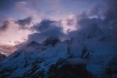 Himalayas landscape. Mountain range with trail in mist and clouds, dark sky with dim sunlight in the background. Stormy weather in mountains. Trekking in Himalaya mountains, Nepal. Nature landscape.