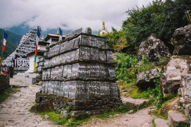 Buddhist religious symbols and inscriptions on the old runes. Prayer walls. Way to Everest base camp. Khumbu valley. Stones with carved ancient buddhist mantras. Everest region, Nepal, Himalayas.
