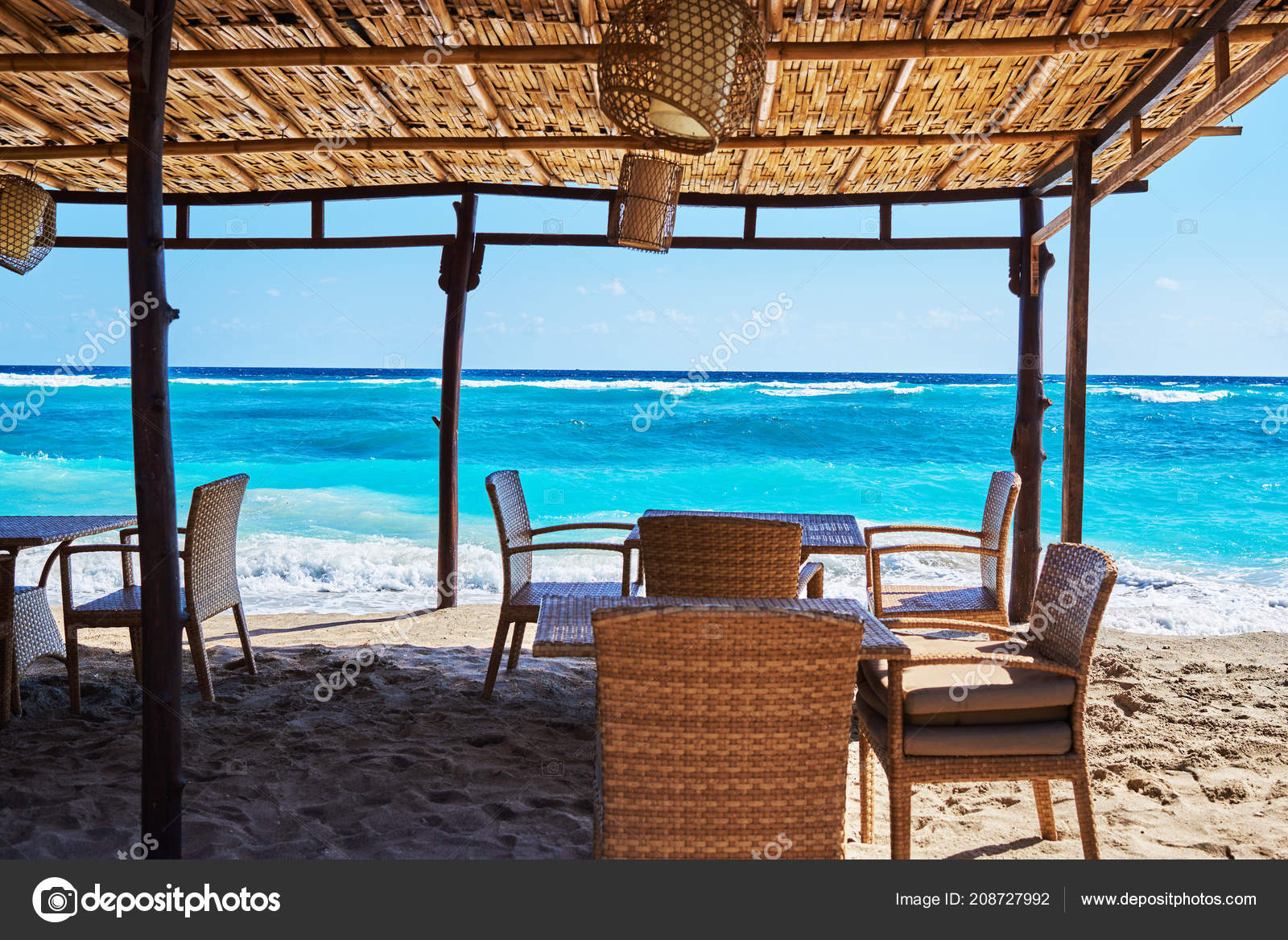 Empty outdoor furniture bar on the beach under the bamboo roof view towards the turquoise ocean summer seascape in the bright day during the high tide