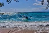Retro dřevěná loď v Korálovém moři. Vlny modrého oceánu na písečné pláži. Ostrov snů pro cestování a odpočinek. Moře úžasné přírodní pozadí. Barva vody a krásně zářivé