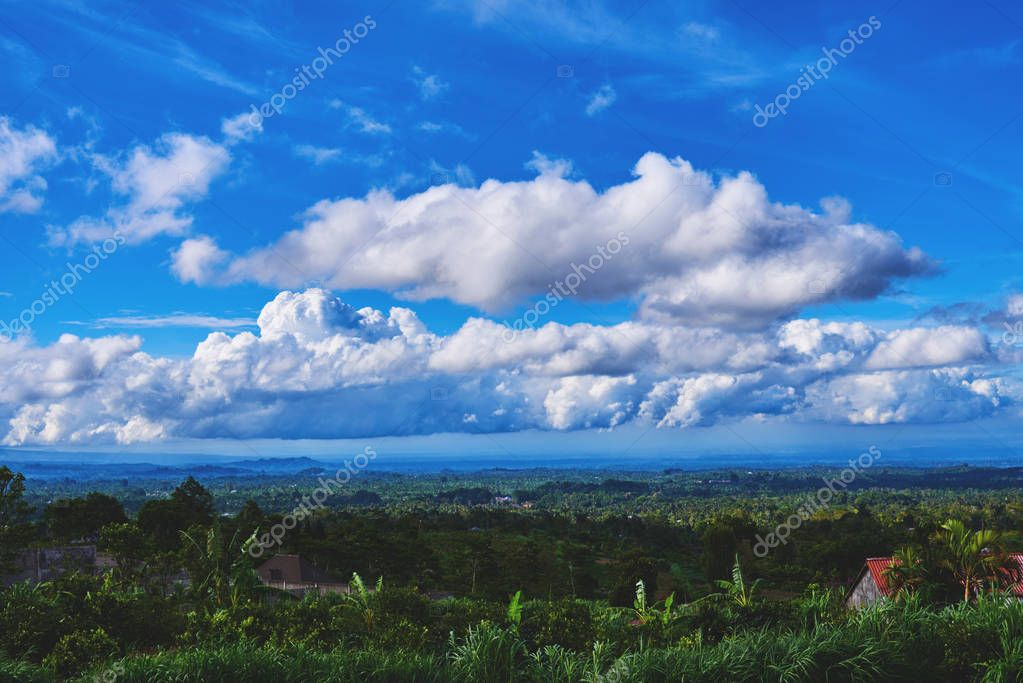 Beautiful spring or summer landscape. Nature wallpaper, background. Green hills and blue sky with white clouds. Landscape of a picturesque green tropical valley. Colourful travel background.