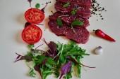 Fotografie Metzger Tomate ist in der Metzgerei, in Portionen frisches Lammfleisch schneiden, würzen, verschiedene Gewürze, Kräuter und aromatische Kräuter, frischen und leichten Salat
