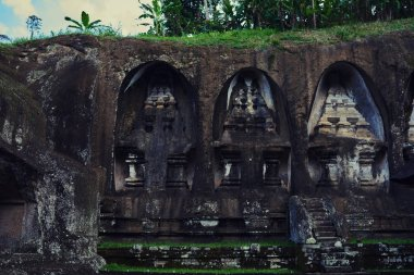 Beautiful view of ancient stone carving of temple on Bali island. Gunung Kawi Temple and Candi in jungle at Bali, Indonesia. Old temples in the jungle. Ancient temple ruins. Carved in stone temple.