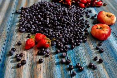 In vintage blue desk light falls through the window blinds on the table scattered blueberries, fresh strawberries, large juicy peaches