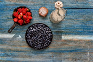 On the table is a vintage wooden carafe of milk and fresh rolls with strawberries and blueberries, berries are in cast iron cookware
