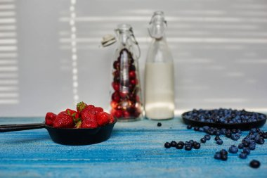 On the kitchen table are two bottles of a transparent glass with milk and the second with strawberries cherries next two pans in kototryh large sprinkling fresh berries