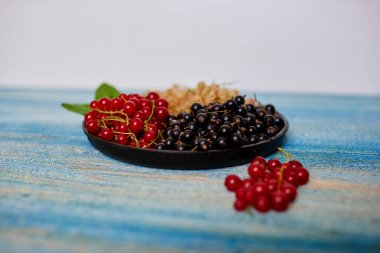 On a white background is a flat cast-iron cookware, there are fresh berries for dessert