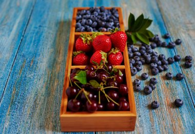 Interesting serving of fresh berries in a wooden form, with several compartments