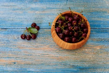 On the wooden kitchen table is a wooden bowl with cherries
