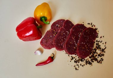 Chef Italian restaurant cut fresh lamb steaks, garlic, red pepper and fresh peppers big one will prigotvlen sauce for meat