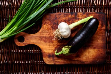 Eggplant, garlic and green onion on the vintage wooden board for cutting