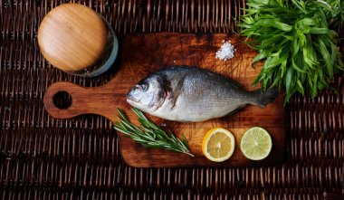 The wife put fresh sea bass on the board, add salt to it and then fry on the grill and served with fresh vegetables, to decorate using green onions, lemon, rosemary sprigs