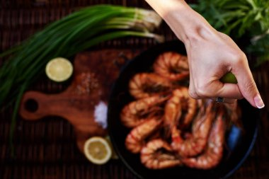 Waitress fish restaurant prepares to issue customers with prawns, fresh seafood are served with lime and green onion, Tiger shrimps fried on a grill in a deep cast iron skille