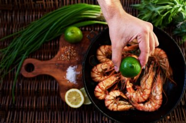In the foreground, a man's hand squeezes a lemon on fried tiger prawns, situated near the green onion bunch of rosemary, In the old cast iron skovordke The royal fried shrimp