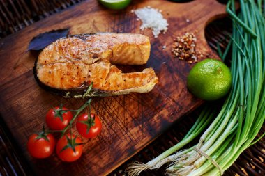 ook restaurant cooked a salmon steak on the grill and served with him a piece of lemon, onion, few tomatoes. Fish lying on a wooden surface, close to her small tomatoes on a branch