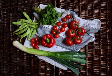 Fresh washed vegetables laid out on a gray linen kitchen towel