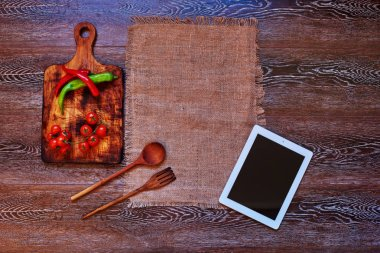 On the kitchen table restaurant chef left his plate and beige linen towel next to which is a wooden board for cutting vegetables and wooden cutlery, On the board is hot peppers and cherry tomatoes