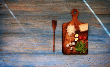 On a wooden shabby retro table is a wooden board for cutting vegetables on it is a piece of Parmesan cheese, quail eggs and cherry tomatoes, near a large wooden fork