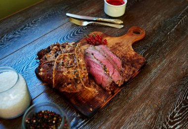 Appetizing veal tenderloin baked in the oven until  blue rare, the cook served on a cutting board, standing next to the sauce to the meat of wild berries