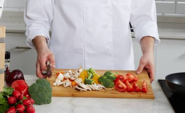 Cook is in a modern bright kitchen, sliced vegetables and mushrooms in salads and hot dishes