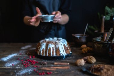 Cooking homemade cake Christmas Eve at home rustic kitchen. Woman's hands make pudding. Ingredients for cooking christmas baking on dark wooden table. Merry Christmas and Happy Holidays! Toned image.