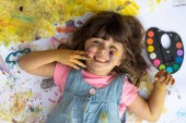 Portrait of cute kid having fun with hands paint. Funny little girl with colored face using watercolours.