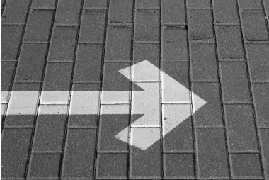 Right pointing arrow on asphalt in black and white.