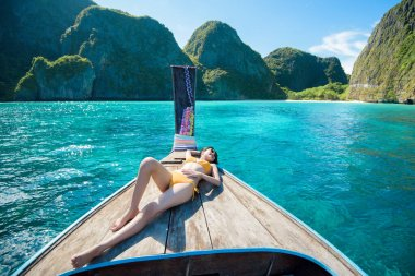 View of woman in swimsuit enjoying on thai traditional longtail Boat over beautiful mountain and ocean, Phi phi Islands, Thailand