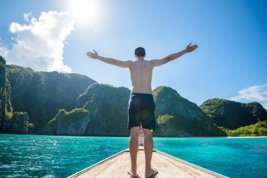 View of man in swimsuit enjoying on thai traditional longtail Boat over beautiful mountain and ocean, Phi phi Islands, Thailand