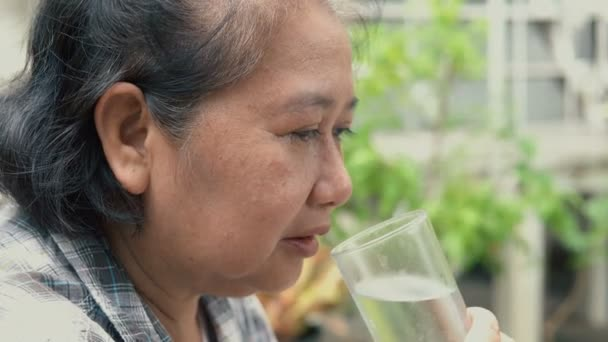 Senior woman drinking a glass of water at park
