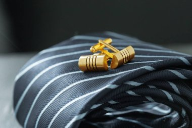 tie and cufflinks on the table .