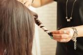 Fotografie Hairstylist curling hair client in hairdressing salon