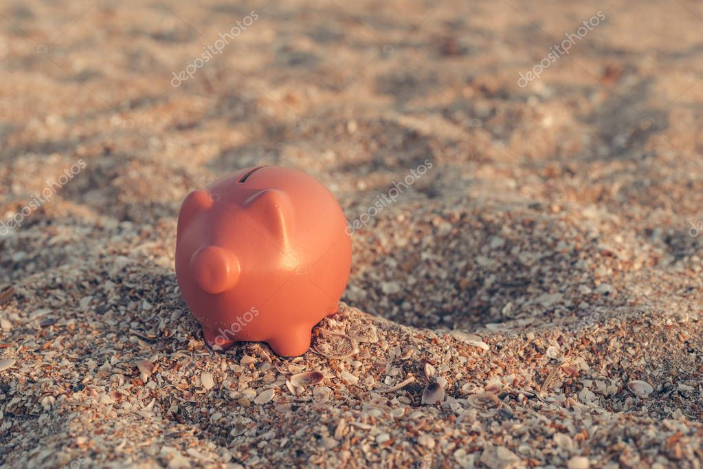 Summer piggy bank on beach