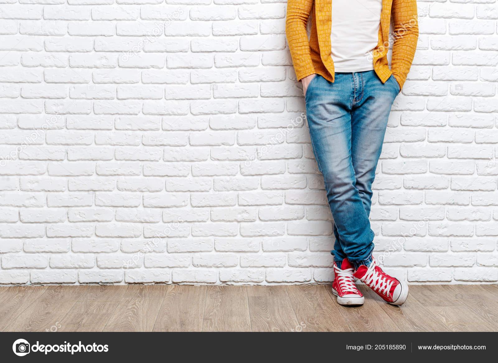 425311063b881 Junge Mode Des Mannes Beine Jeans Und Turnschuhe Auf Holzfußboden ...