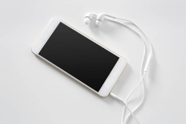 Headphones and smartphone on white background