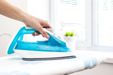 Close up of woman ironing clothes on board