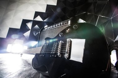 close-up view of electric guitar and classic amplifier on a dark background