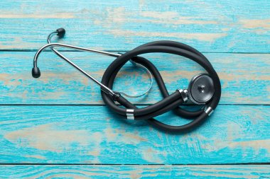 Medical stethoscope on blue wooden background