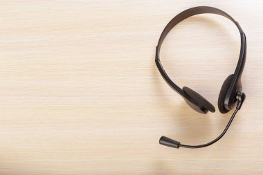 headset with microphone on wooden background
