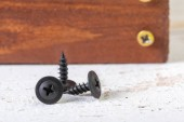 Photo screws on a wooden table, close up view
