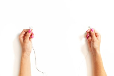 Hands with earphones on white background
