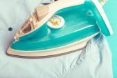 Fotografie Iron on ironing board on light home interior background