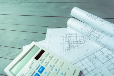 Architectural plans and calculator on wooden background