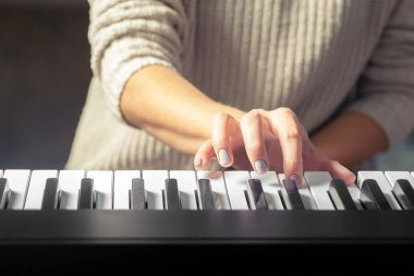 Closeup of hand playing piano, Music and hobby concept