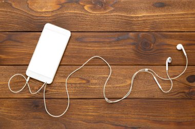 Smartphone and headphones on wooden background, close-up