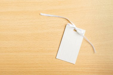Blank tag with white ribbon on wooden background