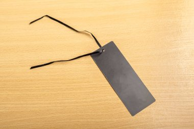 Blank black tag on wooden background